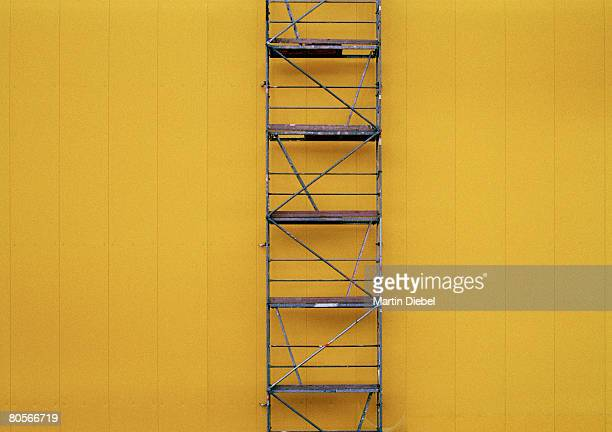 Scaffolding against a yellow wall