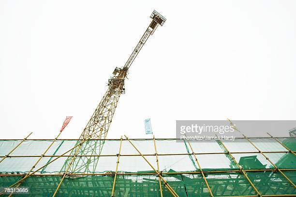 Scaffolding and crane, low angle view