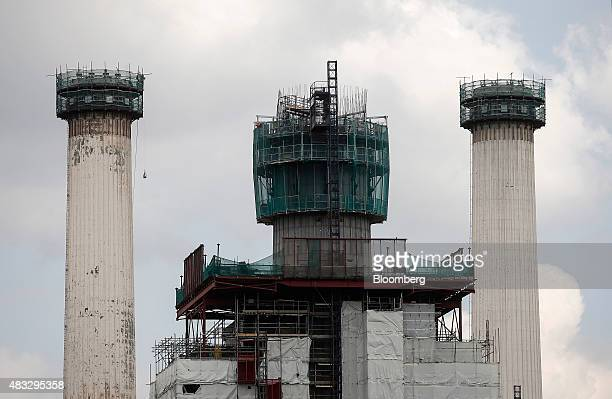 Scaffolding and safety netting surrounds the chimneys of Battersea power station during construction renovation work in London UK on Friday Aug 7...