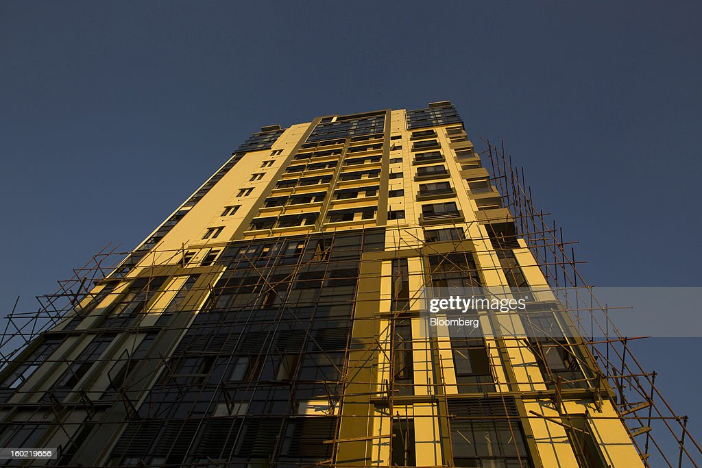 Scaffolding surrounds a condominium building under construction in Yangon, Myanmar, on Tuesday, Jan. 22, 2013. Myanmar cleared about $1 billion in overdue debt with the Asian Development Bank and World Bank using a bridge loan from Japan, opening the door for increased lending as the country seeks to overhaul its infrastructure. Photographer: Brent Lewin/Bloomberg via Getty Images