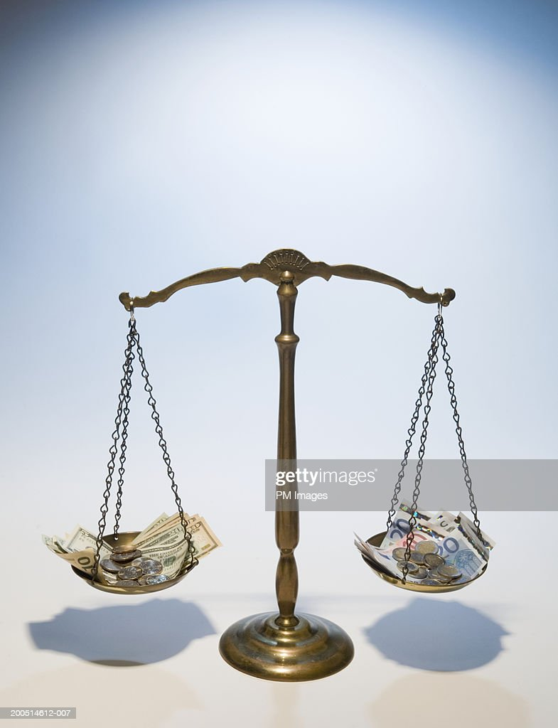 Scales weighing American dollars to Euro notes : Stock Photo