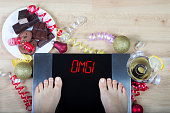 Digital scales with woman feet on them and sign'OMG!' surrounded by christmas decorations, sweets and alcohol. Demonstrates consequences of surfeit and eating unhealthy food during Christmas holidays.