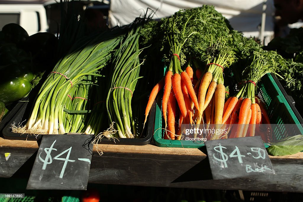 Scallions and carrots are displayed for sale at a stall at the Frenchs Forest Organic Food Market in Sydney, Australia, on Sunday, May 19, 2013. The Reserve Bank of Australia cut its benchmark interest rate to a record low this month to boost businesses weakened by the currency's sustained strength, even as households reacted to earlier reductions. Photographer: Brendon Thorne/Bloomberg via Getty Images