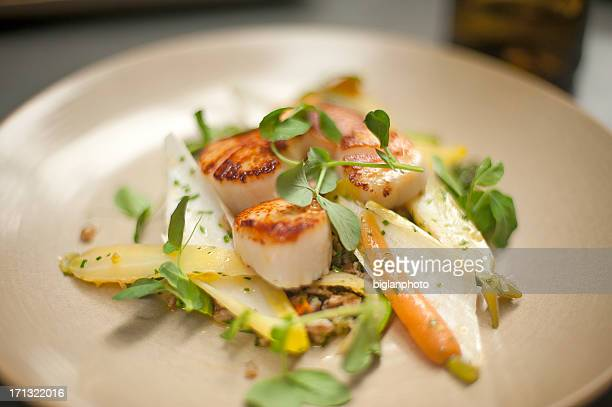 Scallops on a plate with watercress, endive, and baby carrots