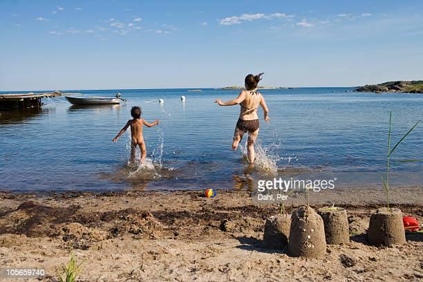 Scandinavia, Sweden, Grisslehamn, rear view of mother and daughter on beach running towards sea