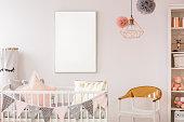 Scandinavian baby room with white crib, chair, bookshelf, wall poster