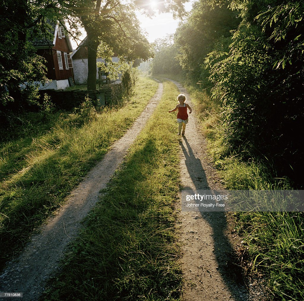 Scandinavian girl running on a country road Oland Sweden.
