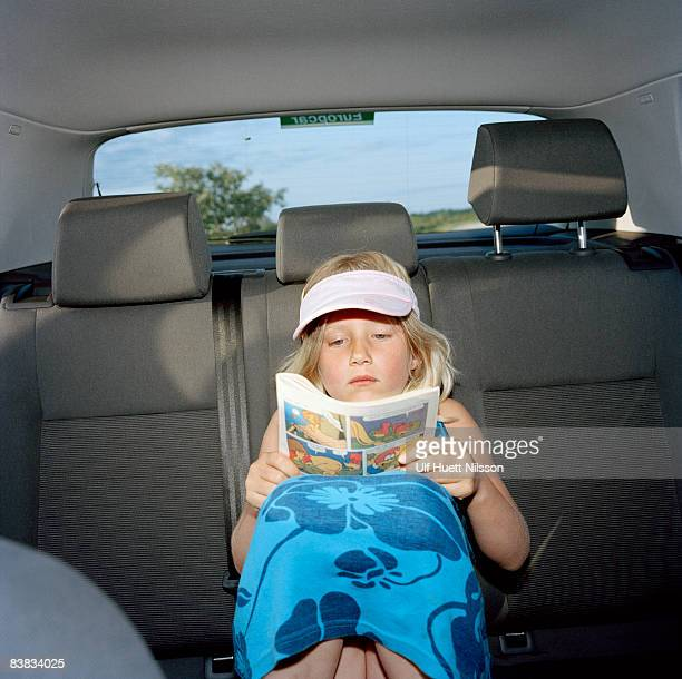 Scandinavian girl sitting in the backseat reading a comic paper Oland Sweden.