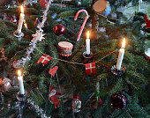 Decorated christmas tree with live candles and parcels underneath.