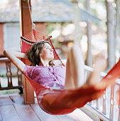 A Scandinavian woman laying in a hammock.