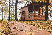 Amazing wooden house exterior located in oak forest near river Kurumka in perfect place in Samara, Russia. Autumn season with yellow leaves and yellow grass. Yellow foliage on the ground.