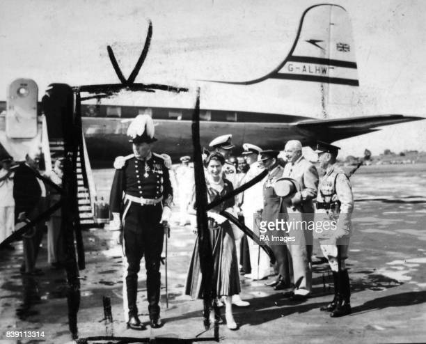 **Scanned lowres from contact** The Queen walks with the Duke of Edinburgh and Sir Andrew Cohen the Governor of Uganda from the Boac Argonaut which...