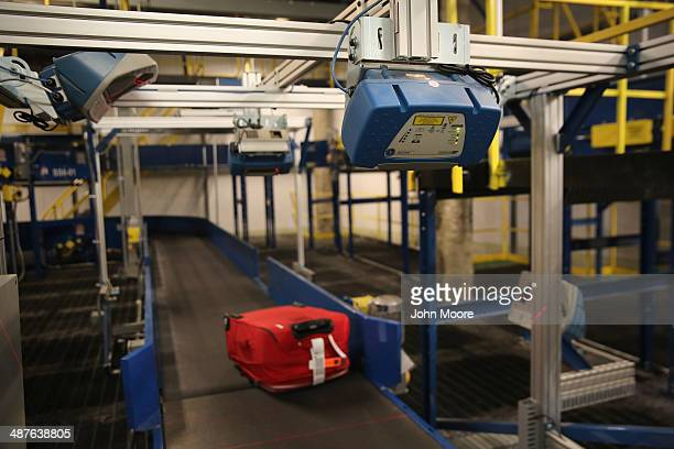 Scanners read bar codes on luggage moving through a new explosives detection system at the Newark Liberty International Airport on May 1 2014 in New...