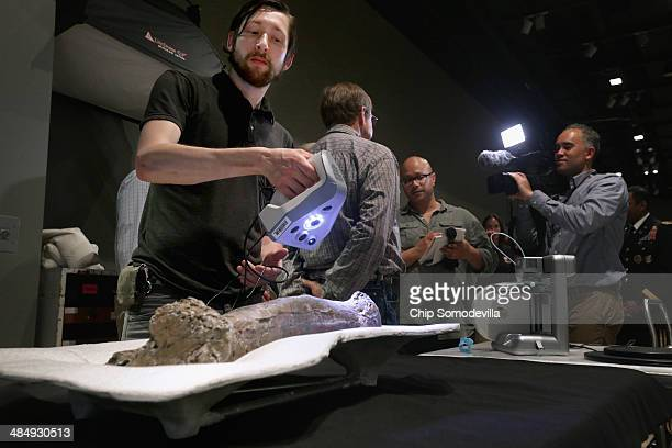 D scanning specialist Jonathan Blundell uses a handheld scanner while making images of the fossilized metatarsal of a 65millionyearold Tyrannosaurus...
