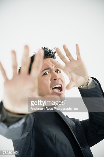 Scared Asian businessman with hands up : Stock Photo