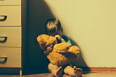 Lonely scared boy sitting in corner, hugging his teddy bear and crying.