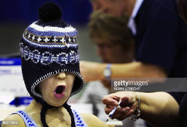 A scared boy pulls his hat over his face while being vaccinated in Rotterdam the Netherlands on March 12 2008 Approximately 3500 children are being...