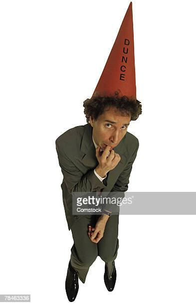 Scared businessman with dunce hat