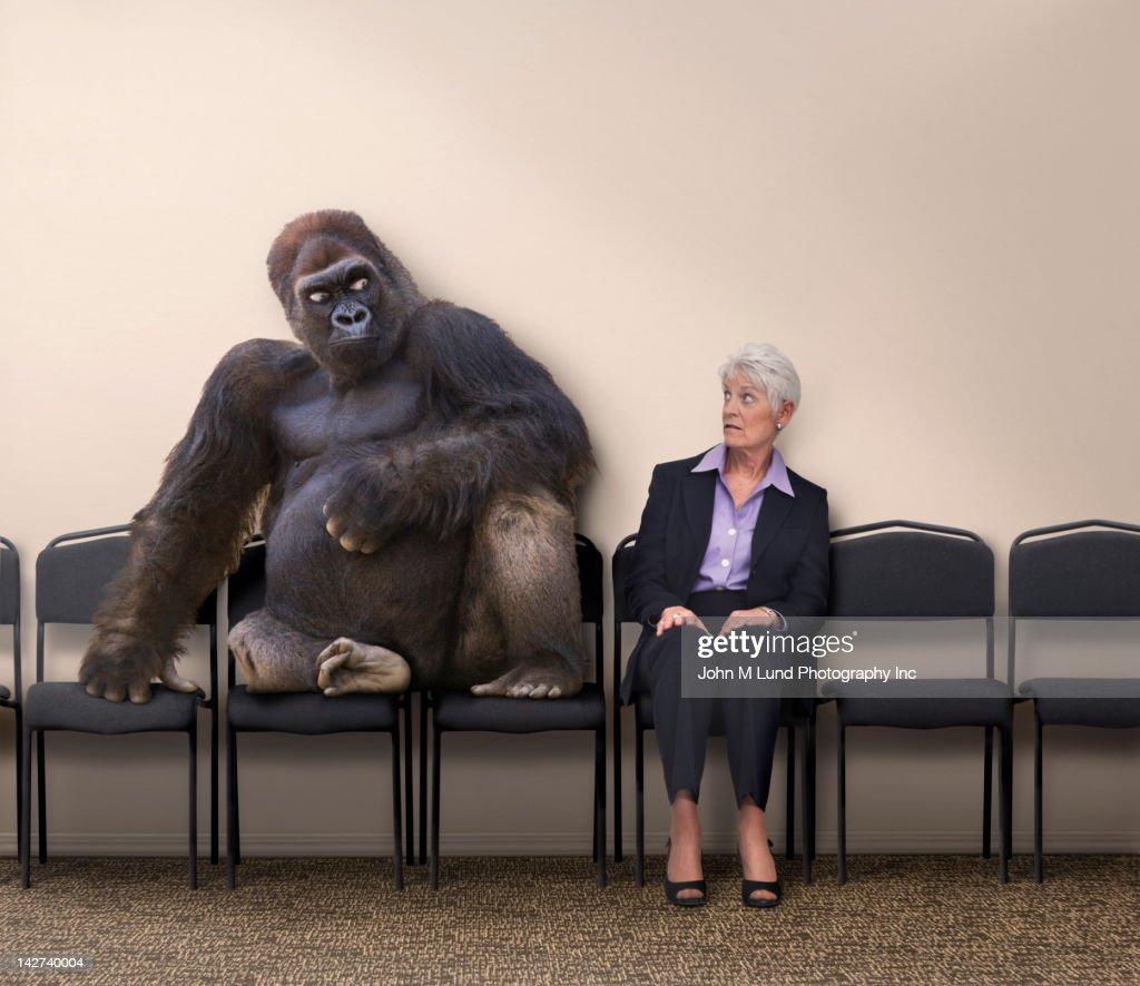 Scared Caucasian woman looking at gorilla