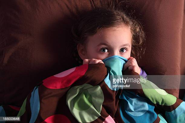 Scared girl covering mouth with covers