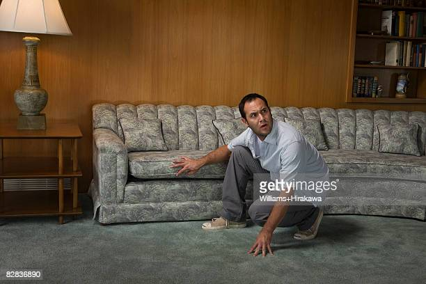 Scared man crouching in front of sofa