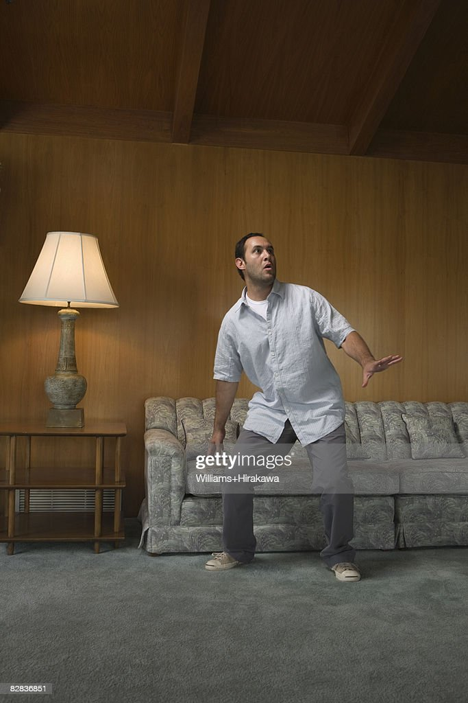 Scared man in front of sofa