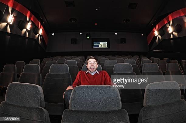 Medo de homem sentado na sala de cinema isolado