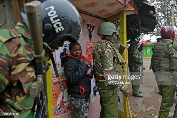 TOPSHOT A scared woman hides behind riot police in Kibera slum in Nairobi on August 12 2017 Three people including a child have been shot dead in...