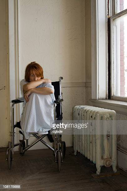 Scared Woman Sitting in Hospital Wheelchair by Window