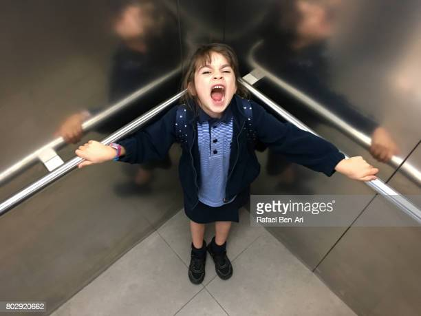 Scared young girl screaming in elevator