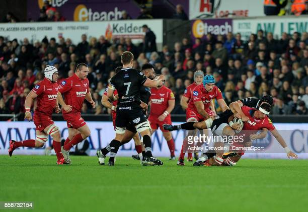 Scarlets' Aaron Shingler is tackled by Ospreys' James King during the Guinness Pro14 Round 6 match between Ospreys and Scarlets at Liberty Stadium on...