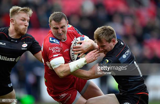 Scarlets centre Hadleigh Parkes is tackled by Nick Tompkins of Saracens during the European Rugby Champions Cup match between Scarlets and Sarcens at...