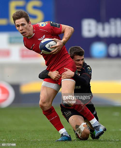 Scarlets fullback Liam Williams escapes the clutches of Saracens scrum half Richard Wigglesworth during the European Rugby Champions Cup match...