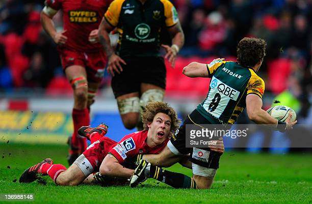Scarlets fullback Liam Williams puts a tackle in on Saints scrum half Martin Roberts during the Pool One Heineken Cup Match between Scarlets and...