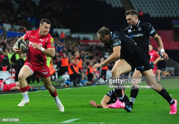 Scarlets' Gareth Davies evades the tackle of Ospreys' Rhys Webb during the Guinness Pro14 Round 6 match between Ospreys and Scarlets at Liberty...