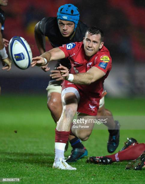 Scarlets scrum half Gareth Davies makes a pass watched by Zach Mercer during the European Rugby Champions Cup match between Scarlets and Bath Rugby...