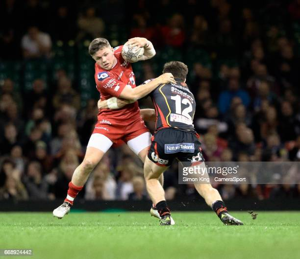 Scarlets' Steffan Evans is tackled by Newport Gwent Dragons' Sam Beard during the Guinness PRO12 Round 20 match between Newport Gwent Dragons and...
