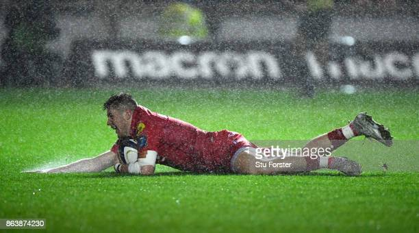 Scarlets wing Steffan Evans dives over for the first try during the European Rugby Champions Cup match between Scarlets and Bath Rugby at Parc y...