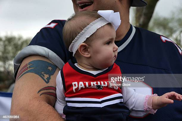 Scarlett 8 months is nestled snuggly in the arms of her father Patriots fan Harry Skigis at a Patriots fan rally at Toso's Sports Bar Grill Skigis is...