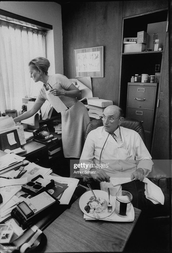 Scarsdale diet Dr. Herman Tarnower sitting w. a healthy lunch at his cluttered desk as assistant Lynne Tryforos works in bkgrd.