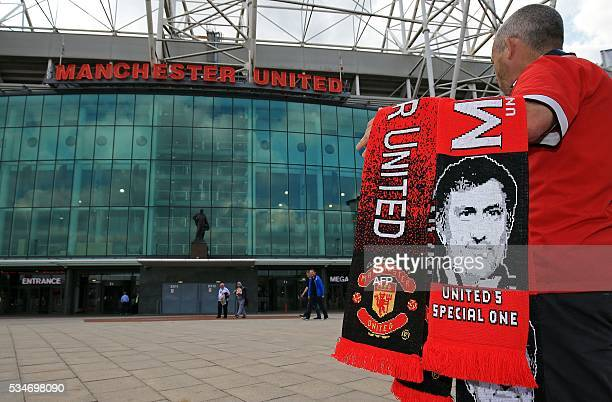 Scarves featuring the image of Manchester United's new Portuguese manager Jose Mourinho are displayed for sale outside the club's Old Trafford...
