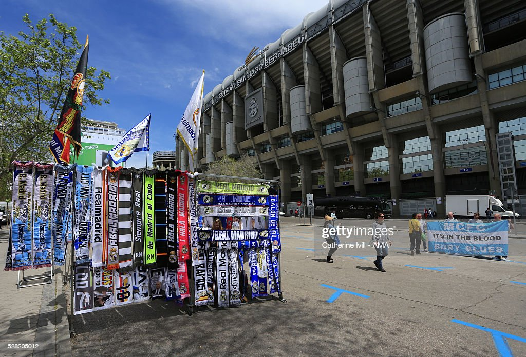 Scarves for sale alongside Manchester City fans having their photo taken outside the stadium prior to the UEFA Champions League Semi Final second leg match between Real Madrid and Manchester City FC at Estadio Santiago Bernabeu on May 4, 2016 in Madrid, Spain.