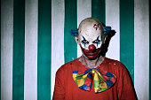 closeup of a scary evil clown wearing a dirty costume, with the circus tent in the background