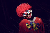 closeup of a scary evil clown wearing a red wig and a dirty costume, in the woods at night