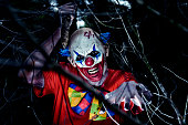 closeup of a scary evil clown wearing a dirty red costume and wielding a big knife, popping in through the branches of a tree in the woods at night
