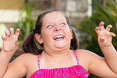 Seven years old caucasian little girl posing making scary face looking at the camera