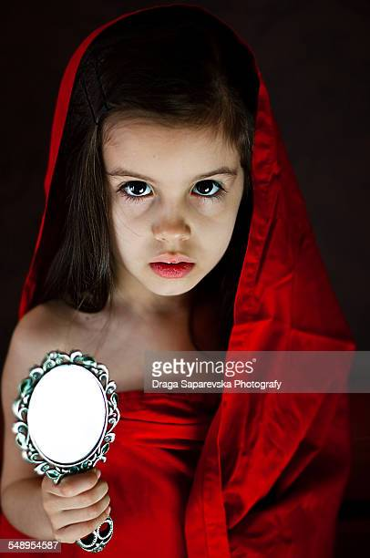 Scary looking little girl holding a mirror