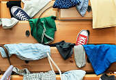 Scattered clothes and shoes in the drawers of the dresser