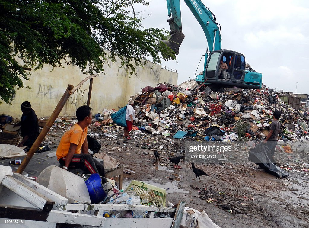 'Scavangers' wait for a digger to turn over rubbish to search for valuable items at a garbage dump in Jakarta on January 29, 2013. Indonesia's National Development Planning Board (BPPN) showed the poverty rate in villages and cities in September 2011 was 12.36 percent compared to September 2012, when the figure was further reduced to 11.66 percent, slightly below the target of 11.5 percent. The government is aiming in 2013 to reduce poverty to as low as 9.5 percent. AFP PHOTO / Bay ISMOYO