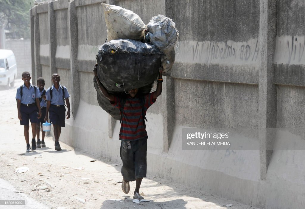 A scavenger carries bags with garbage in a shantytown in Port-au-Prince on March 1, 2013. Brazil began the process of reducing its peace-keeping forces operating under the MINUSTAH mandate from 1910 to 1450 men, the same number that was there before the deadly 2010 earthquake that left a death toll of more than 250,000. AFP PHOTO/VANDERLEI ALMEIDA